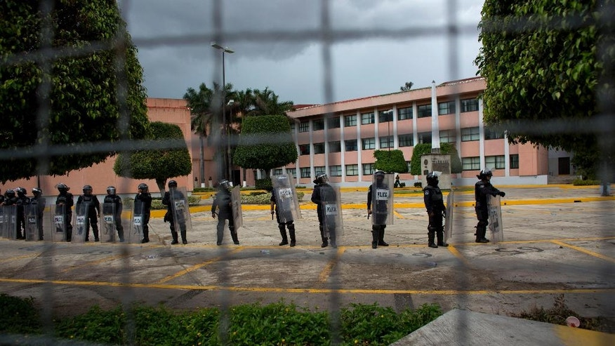 FILE - In this Sept. 26, 2015 file photo, police stand guard around the state Congress building, as people pass by outside the fence, some yelling taunts and hurling rocks, on the one-year anniversary of the disappearance of 43 rural college students in Chilpancingo, Mexico. Within weeks of the September 2014 disappearance of students, Mexican authorities had rounded up scores of suspects and announced they had solved the case. But two independent, international teams of experts subsequently cast doubt on the official investigation, and now the government case has suffered another blow: Accusations of torture by federal police or government troops who arrested the suspects on suspicion of ties to the notoriously violent Guerreros Unidos drug cartel. (AP Photo/Rebecca Blackwell, File)
