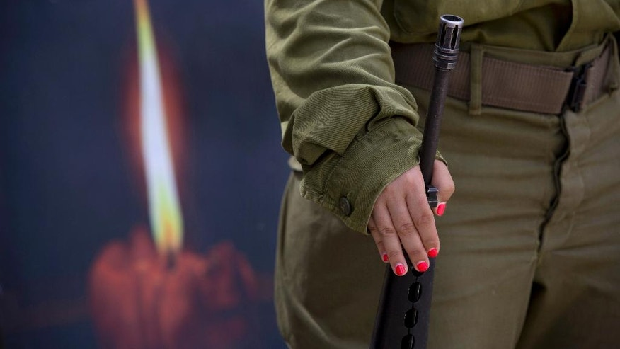 An Israeli soldier takes part in during a rehearsal for a ceremony to mark Israel's Memorial Day for fallen soldiers at the Mount of Olives cemetery in east Jerusalem, Tuesday, May 10, 2016. Israel will mark the annual Memorial Day in remembrance of soldiers who died in the nation's conflicts, beginning at dusk Tuesday until Wednesday evening. (AP Photo/Oded Balilty)