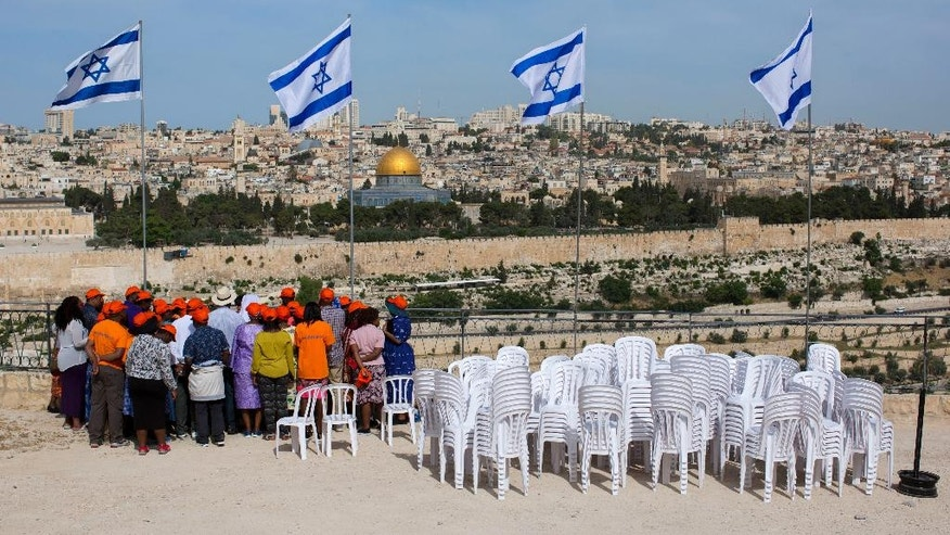 A group of tourists overlook Jerusalem's Old City during preparation for a ceremony to mark Israel's Memorial Day for fallen soldiers at the Mount of Olives cemetery in east Jerusalem, Tuesday, May 10, 2016. Israel will mark the annual Memorial Day in remembrance of soldiers who died in the nation's conflicts, beginning at dusk Tuesday until Wednesday evening. (AP Photo/Oded Balilty)