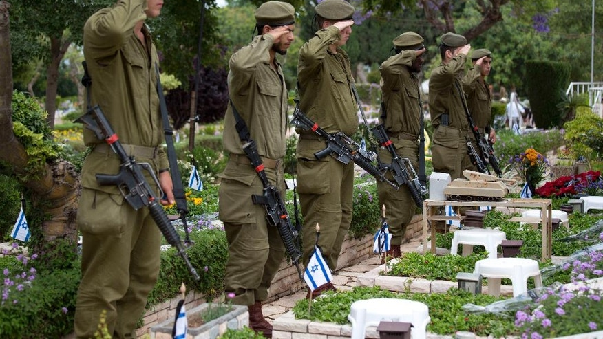 Israeli soldiers salute after placing small flags on the grave of fallen soldiers on the eve of memorial Day in Kiryat Shaul military cemetery in Tel Aviv, Israel, Tuesday, May 10, 2016. Israel marks the annual Memorial Day in remembrance of soldiers who died in the nation's conflicts, beginning at dusk Tuesday until Wednesday evening. (AP Photo/Ariel Schalit)