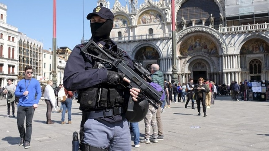 March 24: An Italian masked police officer patrols in St. Mark's square in the Venice lagoon.