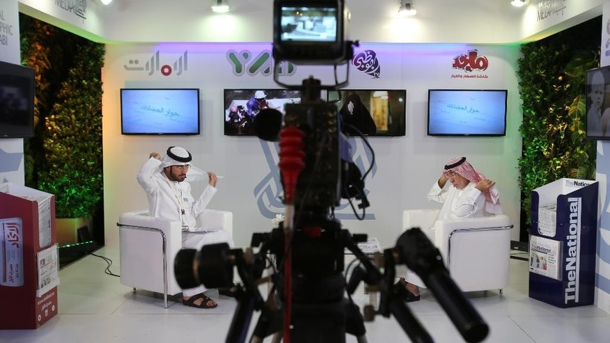 An Emirati television anchor and his guest prepare for a program at the Arab Media Forum in Dubai, United Arab Emirates, Tuesday, May 10, 2016. Jordan's foreign minister is saying that Palestinian statehood is the most important issue now facing the world and fuels the extremism gripping the Mideast. Nasser Judeh made the comment Tuesday at the Arab Media Forum, an event taking place in Dubai, the commercial hub of the United Arab Emirates. (AP Photo/Kamran Jebreili)