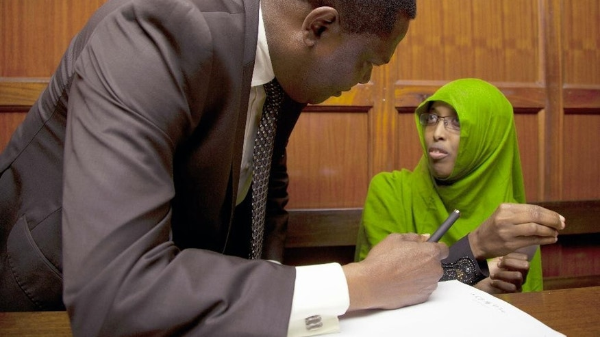 Nuseiba Mohammed Haji talks to her lawyer, Kioko Kilukumi, left, at the Kenya Milimani Law Courts, in Nairobi, Tuesday May 10, 2016. The wife of a Kenyan medic police accuse of plotting a biological attack has been extradited to Kenya from Uganda. Police allege Nuseiba Mohammed Haji, a medical student in Uganda and wife to medical intern Mohammed Ali Abdi, is an accomplice in a foiled plan to launch an anthrax attack in Kenya late April, by a cell of extremist medics. (AP Photo/Sayyid Abdul Azim)