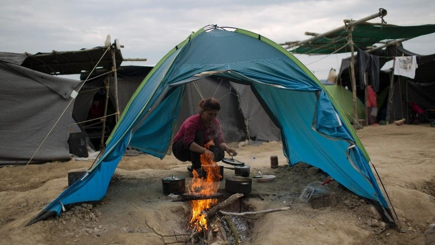 A Kurdish woman cooks on a makeshift fire at the northern Greek border point of Idomeni, Greece, Monday, May 9, 2016. About 54,000 refugees and migrants are currently stranded in Greece as 10,000 are camped in Idomeni, after the European Union and Turkey reached a deal designed to stem the flow of refugees into Europe's prosperous heartland. (AP Photo/Petros Giannakouris)