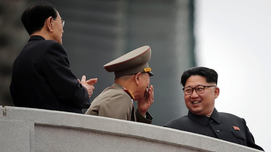 North Korean leader Kim Jong Un, right, smiles at Hwang Pyong So, the top political officer of the Korean People's Army, center, and Kim Yong Nam, the head of North Korea's parliament, left, as they watch parade participants at the Kim Il Sung Square on Tuesday, May 10, 2016, in Pyongyang, North Korea. Hundreds of thousands of North Koreans celebrated the country's newly completed ruling-party congress with a massive civilian parade featuring floats bearing patriotic slogans and marchers with flags and pompoms. (AP Photo/Wong Maye-E)