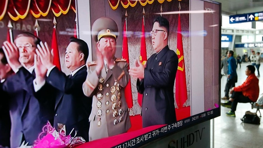 A television news program shows North Korean leader Kim Jong Un, right, applauding during a parade to celebrate the congress of the ruling Workers' Party in Pyongyang, North Korea, at the Seoul Train Station in Seoul, South Korea, Tuesday, May 10, 2016. (AP Photo/Lee Jin-man)