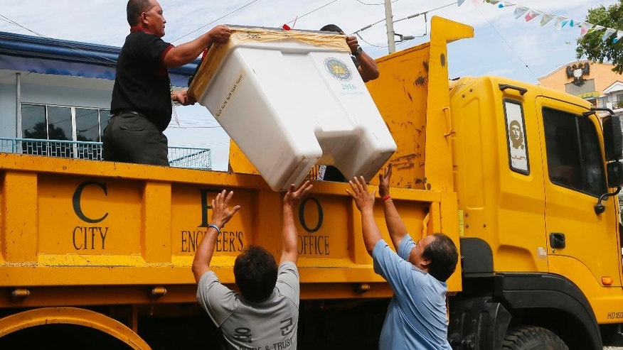 Election workers unload PCOS (Precinct-Count Optical Scanners) machines and other election materials for temporary storage, a day after the country's national elections at leading presidential candidate Rodrigo Duterte's hometown in Davao city in southern Philippines Tuesday, May 10, 2016. Duterte, a brash and tough-talking mayor who has pledged to kill suspected criminals and end crime within six months has secured an unassailable lead in an unofficial vote count. (AP Photo/Bullit Marquez)