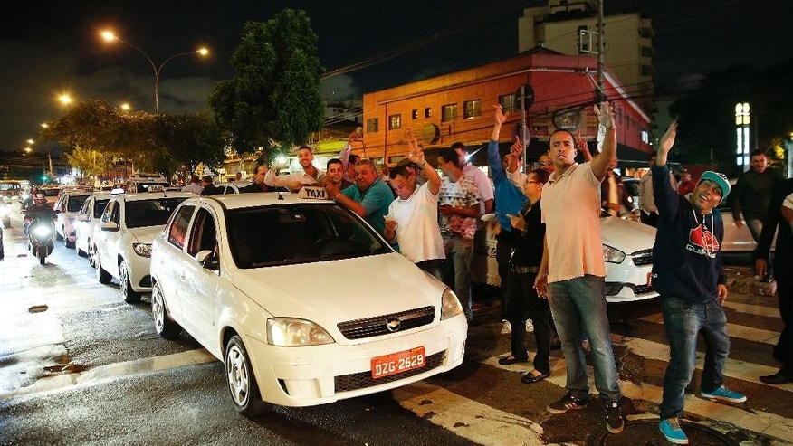 Taxi drivers block a street to protest against the ride-booking company Uber in Sao Paulo, Brazil, Tuesday, May 10, 2016. Sao Paulo Mayor Fernando Haddad has signed a decree authorizing the use of smartphone-based ride-sharing-applications like Uber. (AP Photo/Andre Penner)