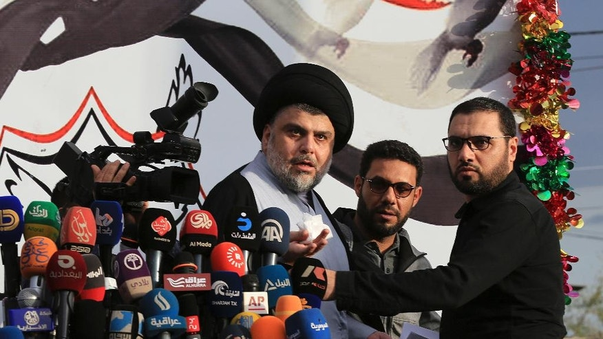 FILE - In this Sunday, March 27, 2016, file photo, Shiite cleric Muqtada al-Sadr, center, prepares to enter the highly fortified Green Zone, in Baghdad, Iraq. After more than a decade of dipping in and out of Iraqi politics, Muqtada al-Sadr, the young Shiite cleric who first made his name fighting U.S. forces in post-2003 Iraq, is leveraging his enduring popular appeal to again roil Iraq's political order. (AP Photo/Karim Kadim, File)