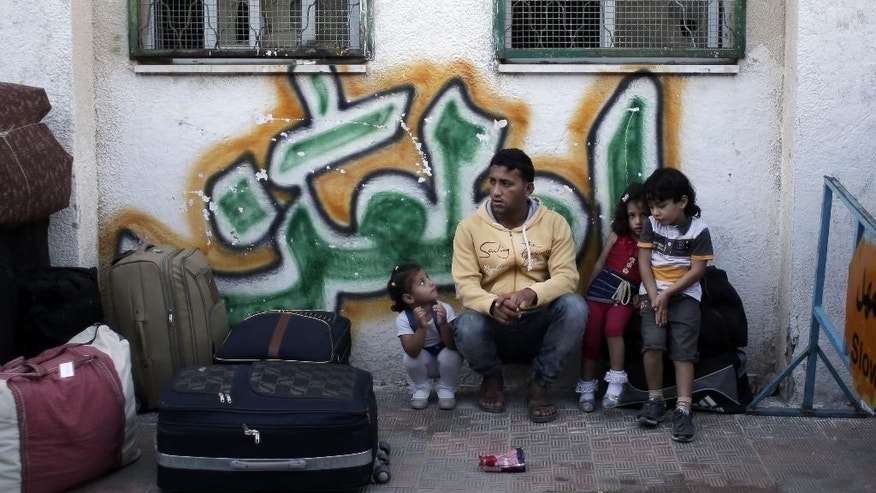 A Palestinian family sit next to their luggage as they wait for their turn to enter the Rafah border crossing with Egypt, in the southern Gaza Strip, Wednesday, May 11, 2016. Hamas says Egypt has temporarily opened its border with the Gaza Strip for the first time in three months. The Rafah crossing, Gaza's main gateway to the outside world, will operate Wednesday and Thursday. (AP Photo/ Khalil Hamra)
