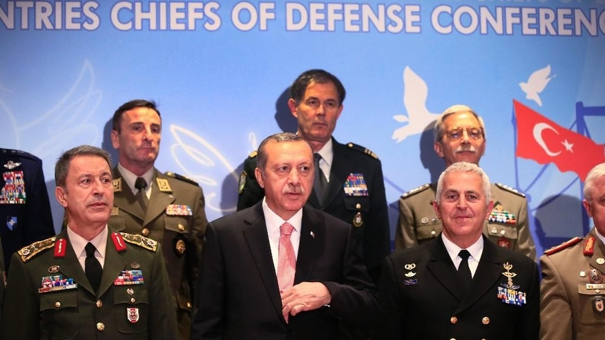 Turkey's President Recep Tayyip Erdogan, centre, poses for photographs with military chiefs of Balkan nations following his speech at their conference, in Istanbul Wednesday, May 11, 2016. Erdogan said Turkish forces have killed some 3,000 Islamic State militants in Syria and Iraq, insisting that no other country has matched Turkey's efforts against the extremist group. At the same meeting earlier however, Turkey's Chief of Staff Gen. Hulusi Akar, left, put the number of IS militants killed Syria and Iraq at 1,300. (AP Photo/Lefteris Pitarakis)