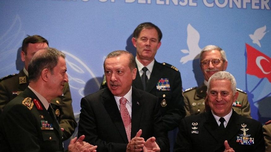 Turkey's President Recep Tayyip Erdogan, centre, talks with Turkey's Chief of Staff Gen. Hulusi Akar, left, as he poses for photographs with military chiefs of Balkan nations following his speech at their conference, in Istanbul Wednesday, May 11, 2016. Erdogan said Turkish forces have killed some 3,000 Islamic State militants in Syria and Iraq, insisting that no other country has matched Turkey's efforts against the extremist group. At the same meeting earlier however, Akar, left, put the number of IS militants killed Syria and Iraq at 1,300. (AP Photo/Lefteris Pitarakis)