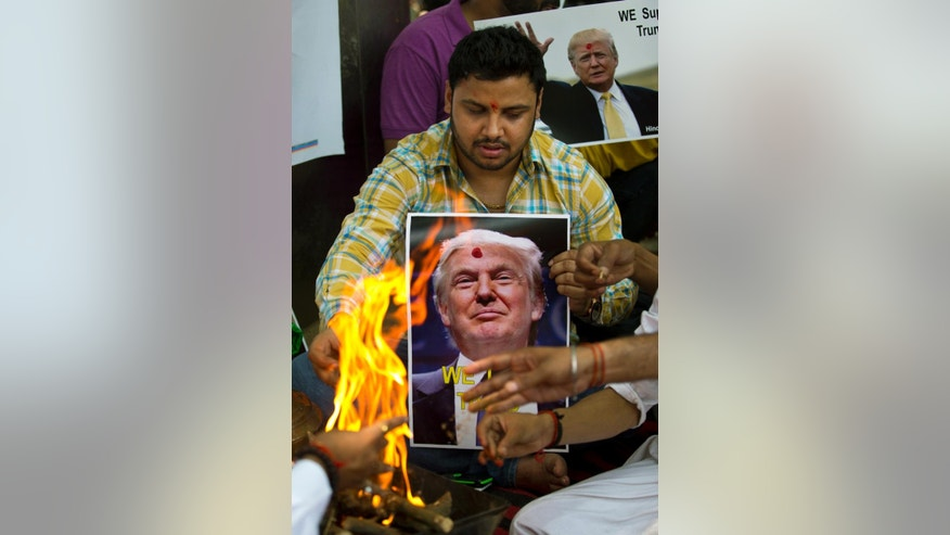 Activists of right-wing Hindu Sena or Hindu Army make offerings to the fire god while conducting Hindu rituals to ensure a win for U.S. presidential candidate Donald Trump in New Delhi, India, Wednesday, May 11, 2016. While Trump has dominated the Republican primary race to decide the party's candidate for the November election, his calls for temporarily banning Muslims from America and cracking down on terrorist groups abroad have earned him some fans in faraway India. (AP Photo/Saurabh Das)