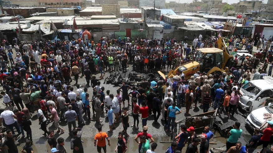 A municipality bulldozer cleans up while citizens inspect the scene after a car bomb explosion at a crowded outdoor market in the Iraqi capital's eastern district of Sadr City, Iraq, Wednesday, May 11, 2016. An explosives-laden car bomb ripped through a commercial area in a predominantly Shiite neighborhood of Baghdad on Wednesday, killing and wounding dozens of civilians, a police official said. (AP Photo/ Khalid Mohammed)