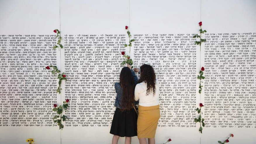 Two girls hang roses on the wall of names of fallen soldiers, at the Armored Corps memorial, before a ceremony marking the annual Memorial Day for soldiers and civilians killed in more than a century of conflict between Jews and Arabs, in Latrun near Jerusalem, Israel, Wednesday, May 11, 2016. Israel came to a standstill on Wednesday as sirens wailed across the country on its annual Memorial Day for fallen soldiers and victims of terrorism. (AP Photo/Ariel Schalit)