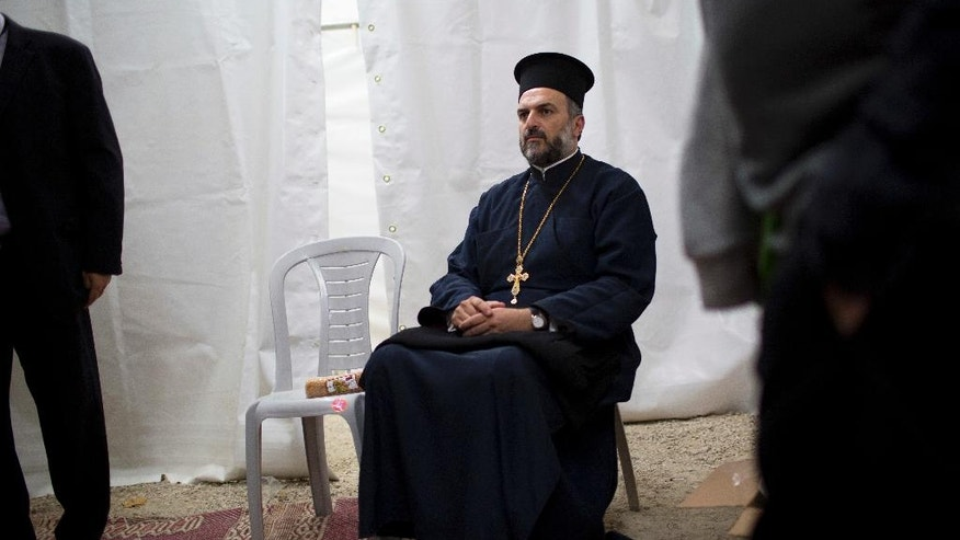 In this Monday, May 9, 2016 photo, Father Gabriel Naddaf who will light a torch this week in Israel's official independence day ceremony, arrives to the rehearsal for the upcoming ceremony in Jerusalem. Israel's decision to honor a controversial Greek Orthodox priest at its official independence day ceremony is driving a wedge in the country's tiny Christian Arab community as the government recognizes him for his crusade to encourage his followers to enlist in the Israeli military. (AP Photo/Oded Balilty)