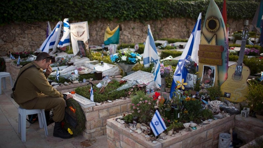 An Israeli soldier visits the grave of his friend on the Memorial Day eve commemorating fallen soldiers, at the military cemetery at Mount Hertzl in Jerusalem, Tuesday, May 10, 2016. Israel will mark the annual Memorial Day in remembrance of soldiers who died in the nation's conflicts, beginning at dusk Tuesday until Wednesday evening. (AP Photo/Oded Balilty)