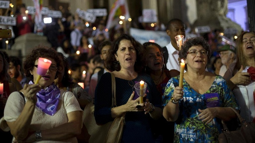 Demonstrator shouts pro-government slogans as they hold candles during a protest against the impeachment proceeding of Brazil's President Dilma Rousseff, in Rio de Janeiro, Brazil, Tuesday, May 10, 2016. Rousseff supporters displayed their frustration Tuesday, with rallies held in cities in more than a dozen states. Protesters occupied roads and highways, blocked university entrances and burned tires. (AP Photo/Silvia Izquierdo)
