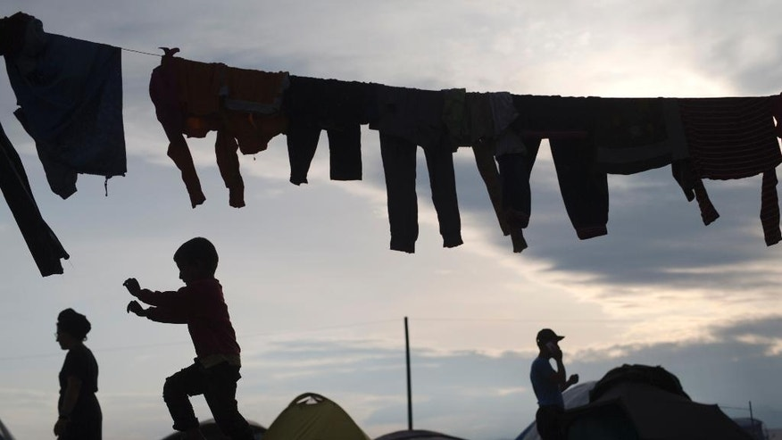 Clothes hang over a rope as refugees walk in front of tents at the northern Greek border point of Idomeni, Greece, on Tuesday May 10, 2016. About 54,000 refugees and migrants are currently stranded in Greece with 10,000 camped in Idomeni, after the European Union and Turkey reached a deal designed to stem the flow of refugees into Europe's prosperous heartland. (AP Photo/Petros Giannakouris)