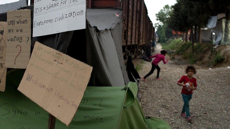 Children walk next to a train carriage behind placards, at the northern Greek border point of Idomeni, Greece, on Tuesday May 10, 2016. About 54,000 refugees and migrants are currently stranded in Greece with 10,000 camped in Idomeni, after the European Union and Turkey reached a deal designed to stem the flow of refugees into Europe's prosperous heartland. (AP Photo/Petros Giannakouris)