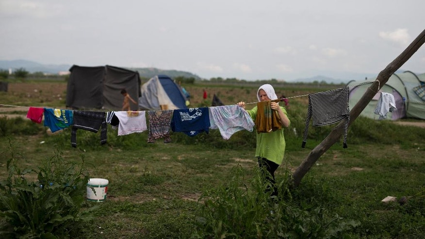 A woman hangs out clothes  at the northern Greek border point of Idomeni, Greece, on Wednesday May 11, 2016. About 54,000 people are currently stranded in Greece as 10,000 are camped in Idomeni, after the European Union and Turkey reached a deal designed to stem the flow of refugees into Europe's prosperous heartland. (AP Photo/Petros Giannakouris)