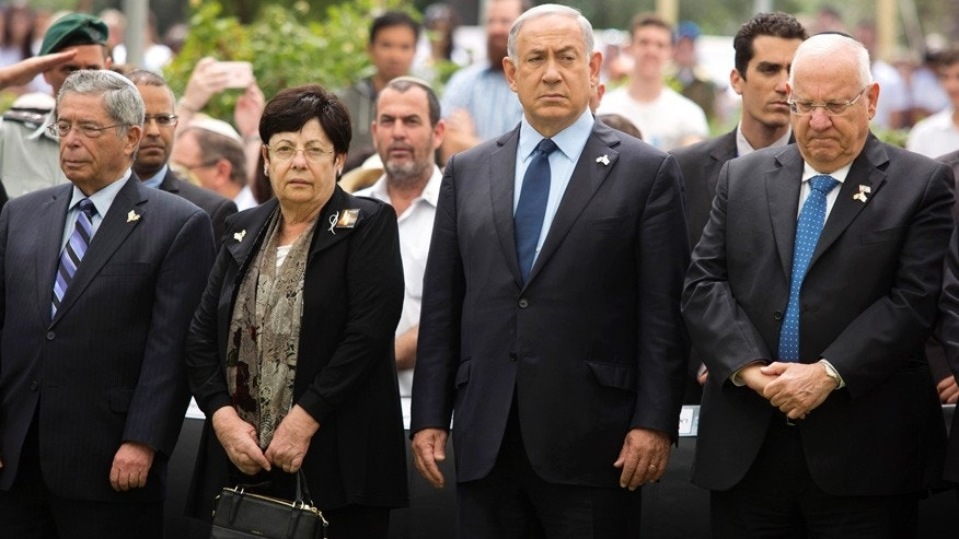 May 11, 2016: Israeli Prime Minister Benjamin Netanyahu (center) stands with President Reuven Rivlin during an official state Memorial Day service for the country's fallen soldiers and victims of terrorism with a two minute siren during a ceremony held on Mount Herzl Cemetery.
