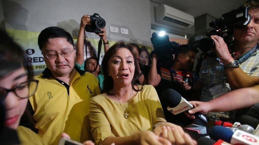 "Philippine vice presidential candidate Maria Leonor ""Leni"" Robredo, center, talks to reporters after a press conference in suburban Quezon city, north of Manila, Philippines, Tuesday, May 10, 2016. Robredo is slightly ahead of Sen. Ferdinand ""Bongbong"" Marcos Jr., the son of the late strongman, in an unofficial count of votes for the vice president. (AP Photo/Aaron Favila)"