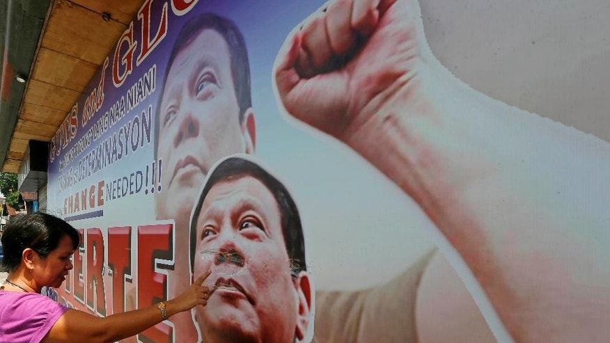 A resident checks the damage of a tarpaulin billboard of leading presidential candidate Mayor Rodrigo Duterte along a boulevard at his hometown in Davao city in southern Philippines Wednesday, May 11, 2016. Duterte has widened his lead in an unofficial tally but still refuses to claim victory. (AP Photo/Bullit Marquez)