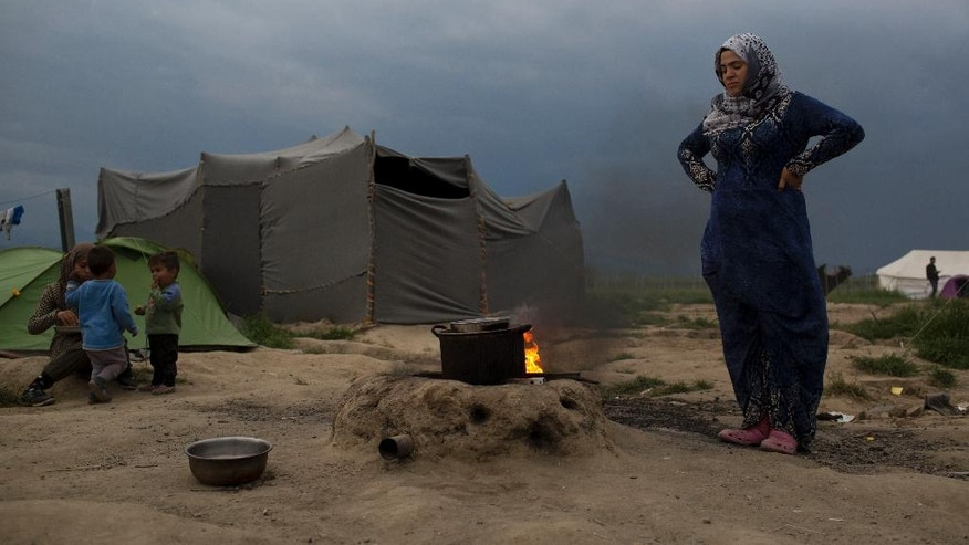 A Syrian woman cooks at the northern Greek border point of Idomeni, Greece, on Tuesday May 10, 2016. About 54,000 refugees and migrants are currently stranded in Greece as 10,000 are camped in Idomeni, after the European Union and Turkey reached a deal designed to stem the flow of refugees into Europe's prosperous heartland. (AP Photo/Petros Giannakouris)