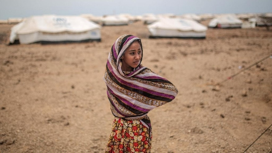 FILE- In this Tuesday, May 19, 2015 file photo, Ashwaq, 12, stands outside her family's tent, at the Markaze refugee camp in Obock, northern Djibouti. The Middle East has accounted for more than 50 per cent of the world's population internally displaced by conflict in 2015, with nearly 4.8 million new people forced to flee their homes. A major aid agency says 27.8 million people around the world were internally displaced by conflict and natural disasters last year, or as many as the combined populations of New York City, London, Paris and Cairo. (AP Photo/Mosa'ab Elshamy, File)