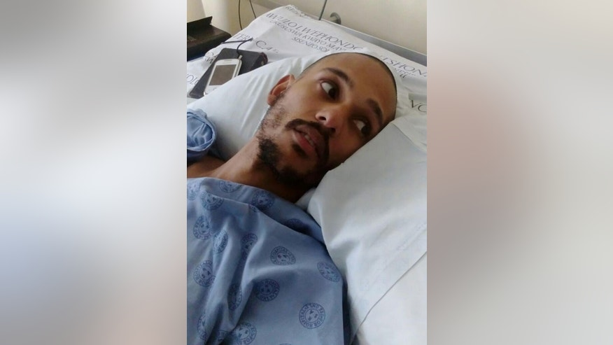 An injured Darryn August lays in his hospital bed in Cape Town, Wednesday, May 11, 2016 after he was thrown from a moving train by assailants last week. He is now paralyzed from the waist down, prompting a flow of donations for what is expected to be a long, costly rehabilitation. (AP Photo/Edwin Brooks)