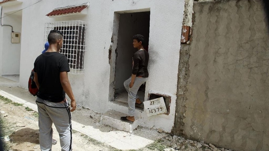 Neighbors gather at the entrance of a house in which elite police squads have killed two armed terrorists and arrested 16 others in an operation in the Menihla area, outside Tunis, Wednesday, May 11, 2016. The ministry did not elaborate on the plans it hopes the police have foiled, nor the identity of those killed and arrested. (AP PHOTO/Hassene Dridi)