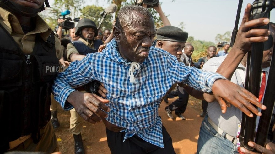 FILE - In this Monday, Feb. 22, 2016 file photo, Uganda's main opposition leader Kizza Besigye, center, is arrested by police and thrown into the back of a blacked-out police van, outside his home in Kasangati, Uganda. Besigye was arrested again Wednesday, May 11, 2016 ahead of the inauguration Thursday of the country's long-time president Yoweri Museveni, while access to social media sites like Facebook and Twitter appeared to have been blocked by a government censor. (AP Photo/Ben Curtis, File)