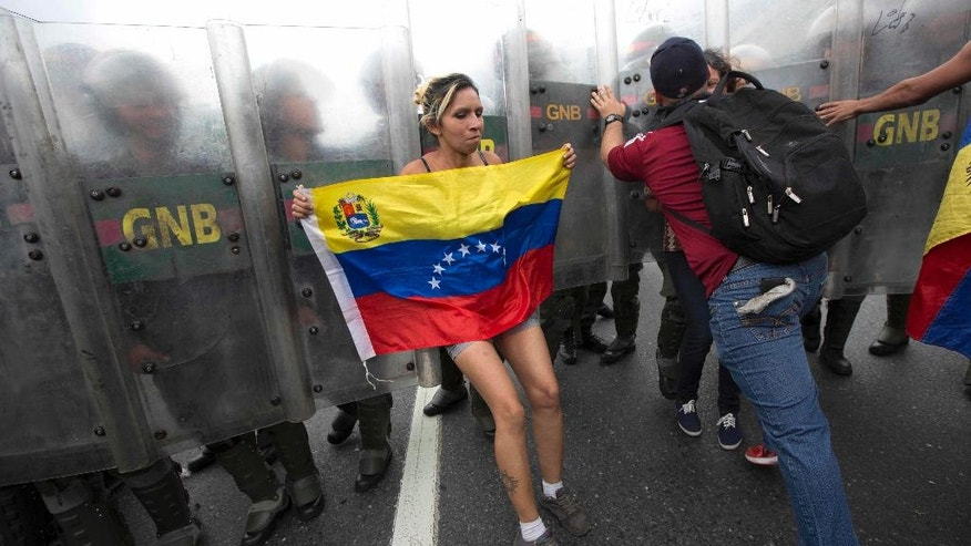 A protester with a Venezuelan flag is pushed away by National Guard soldiers trying to keep demonstrators from reaching the National Electoral Council (CNE) in Caracas, Venezuela, Wednesday, May 11, 2016. The opposition is marching against the country's administration, demanding that election officials start counting signatures that could lead to a presidential recall vote. (AP Photo/Ariana Cubillos)