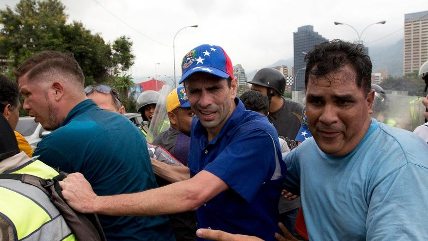 Opposition leader Henrique Capriles, center, reacts to the effects of pepper gas as he is led away by his bodyguards after soldiers fired the gas to repel marchers protesting against the government, in Caracas, Venezuela, Wednesday, May 11, 2016. Thousands of Venezuelans are marching against the country's socialist administration, demanding that elections officials start counting signatures that could lead to a presidential recall vote. (AP Photo/Fernando Llano)