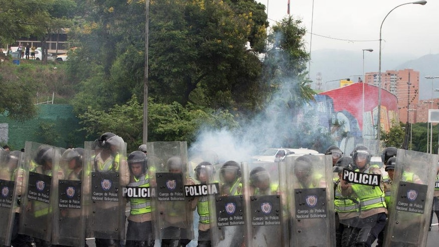 Bolivarian National Police advance as they fire tear gas at anti-government protesters to keep them from reaching the National Electoral Council (CNE) in Caracas, Venezuela, Wednesday, May 11, 2016.  The opposition is marching to demand election officials start counting signatures that could lead to a presidential recall vote. (AP Photo/Fernando Llano)