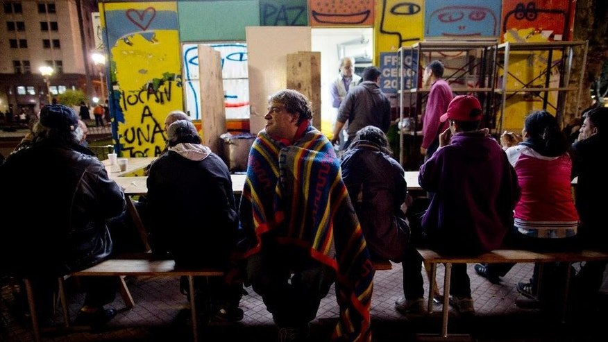 In this May 9, 2016 photo, Claudio Omar Gonzalez, 42, covers himself with a blanket as he waits with others for free food at a soup kitchen outside the government house in Plaza de Mayo in Buenos Aires, Argentina. Gonzalez, who sells candy on the city's trains, says he struggles to buy the products he needs because prices keep going up. Inflation in April reached 6.5 percent, according to the Buenos Aires statistics office, the highest in 14 years. (AP Photo/Natacha Pisarenko)