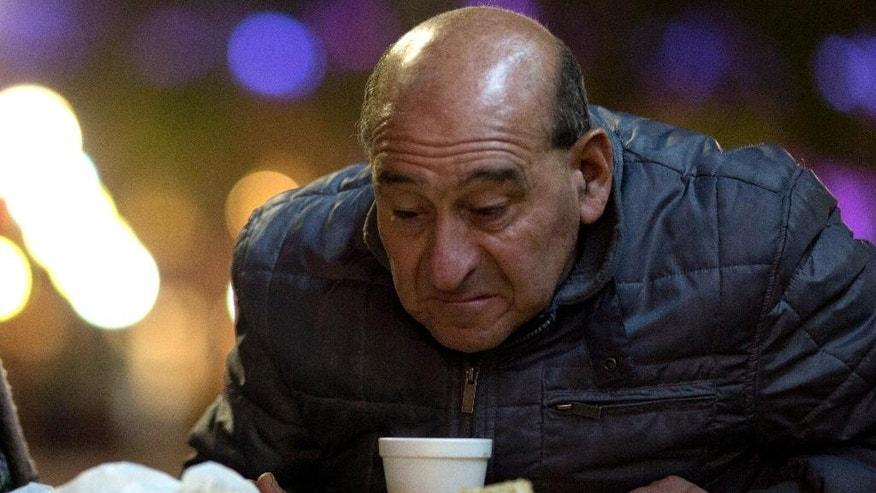 In this Monday, May 9, 2016 photo, a man sits down to eat a free dinner at a soup kitchen outside the government house in Plaza de Mayo  in Buenos Aires, Argentina. Inflation in April reached 6.5 percent, according to the Buenos Aires statistics office, the highest in 14 years. (AP Photo/Natacha Pisarenko)