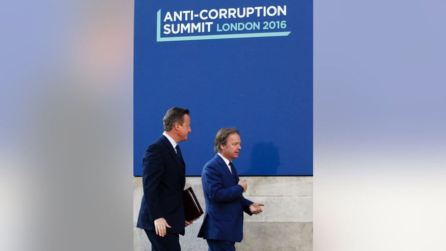 Britain's Prime Minister David Cameron is welcomed by Hugo Swire as he arrives for the Anti-Corruption Summit in London, Thursday, May 12, 2016.(AP Photo/Frank Augstein)