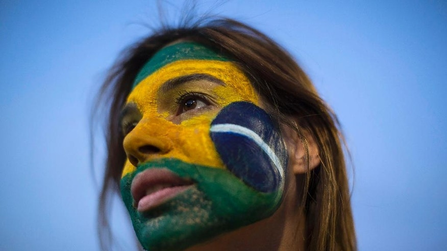 An anti-government demonstrator shows off her Brazilian flag motif face paint outside Congress in Brasilia, Brazil, Wednesday, May 11, 2016. Brazil's Senate is nearing a historic vote on impeaching President Dilma Rousseff, likely ending 13 years of government by her party amid a spate of crises besetting Latin America's largest nation. (AP Photo/Felipe Dana)