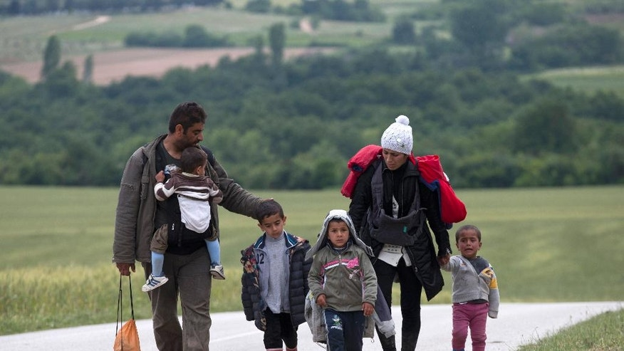 A family walk on their way to Idomeni camp, Greece, after a group of migrants and refugees tried to cross the Macedonia's border, Wednesday, May 11, 2016. Around 9500 stranded refugees and migrants are camped at the makeshift refugee camp of the northern Greek border point of Idomeni. (AP Photo/Petros Giannakouris)