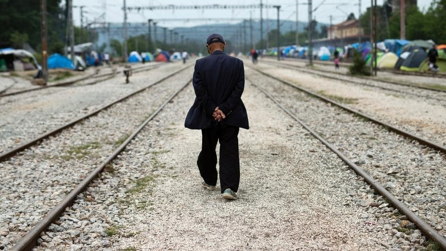 A man walk among railway tracks at  a makeshift refugee camp of the northern Greek border point of Idomeni, Greece, on Thursday, May 12, 2016. About 54,000 people are currently stranded in Greece, after the European Union and Turkey reached a deal designed to stem the flow of refugees into Europe's prosperous heartland. (AP Photo/Petros Giannakouris)