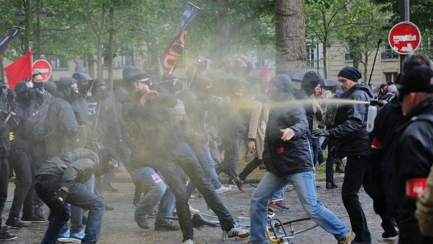 Demonstrators, left, clash with Unions security men during a protest against Labor Law as the Socialist government decided to force the bill through Parliament without a vote, in Paris, Thursday, May 12, 2016. France's government is facing a major test as lawmakers hold a no-confidence vote, prompted by a deeply divisive labor law allowing longer workdays and easier layoffs.(AP Photo/Christophe Ena)