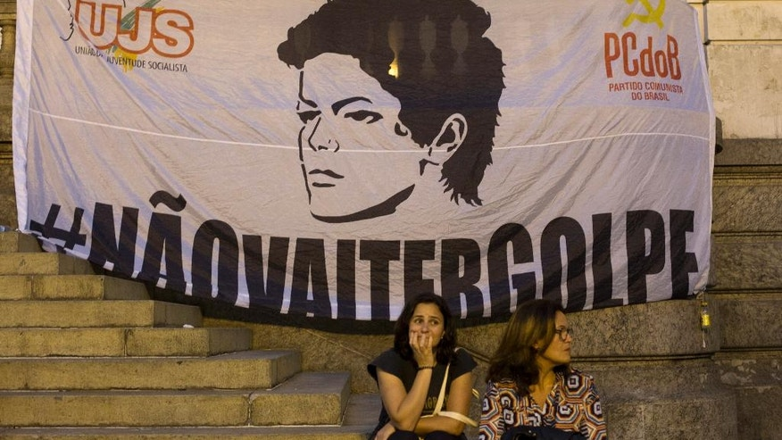 "Pro-government demonstrators gather near a banner that shows the face of Brazil's President Dilma Rousseff and reads in Portuguese ""There won't be a coup"" during a protest against her impeachment in Rio de Janeiro, Brazil, Wednesday, May 11, 2016. Brazil's Senate is nearing a historic vote on impeaching Rousseff, likely ending 13 years of government by her party amid a spate of crises besetting Latin America's largest nation. (AP Photo/Silvia Izquierdo)"