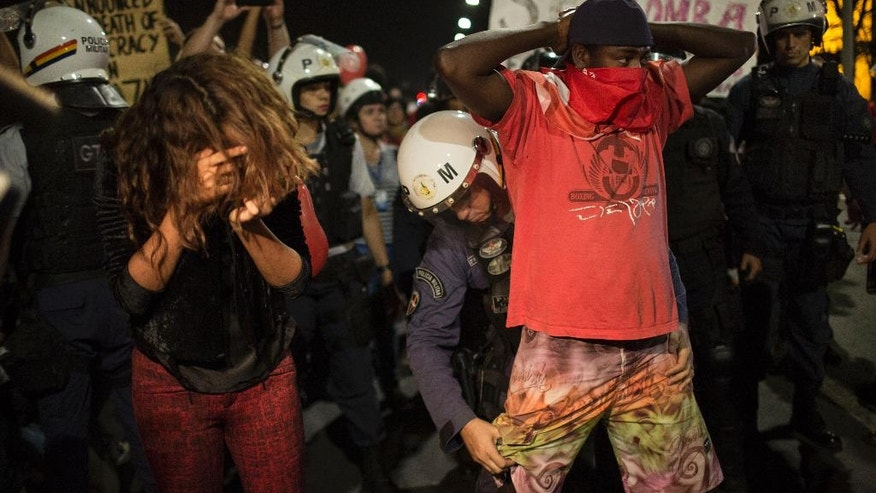 A pro-government supporter is frisked after clashing with the police when he attempted to advance towards the Congress building, in Brasilia, Brazil, Wednesday, May 11, 2016. Brazil's Senate is nearing a historic vote on impeaching President Dilma Rousseff, likely ending 13 years of government by her party amid a spate of crises besetting Latin America's largest nation. (AP Photo/Felipe Dana)