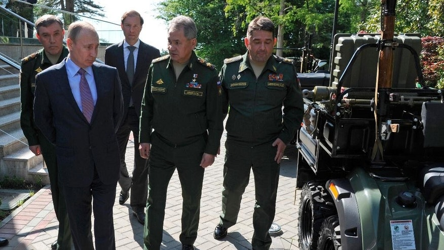 Russian President Vladimir Putin, left, inspects military vehicles after a meeting with military and defense industries' officials in the Bocharov Ruchei residence in Sochi, Russia, Thursday, May 12, 2016. The meeting focused on production goals for defense industries. At center, Defense Minister Sergei Shoigu; at left back, Chief of the General Staff of the Russian Armed Forces Valery Gerasimov; second left back, Industry and Trade Minister Denis Manturov. (Mikhail Klimentyev/Sputnik, Kremlin Pool Photo via AP)