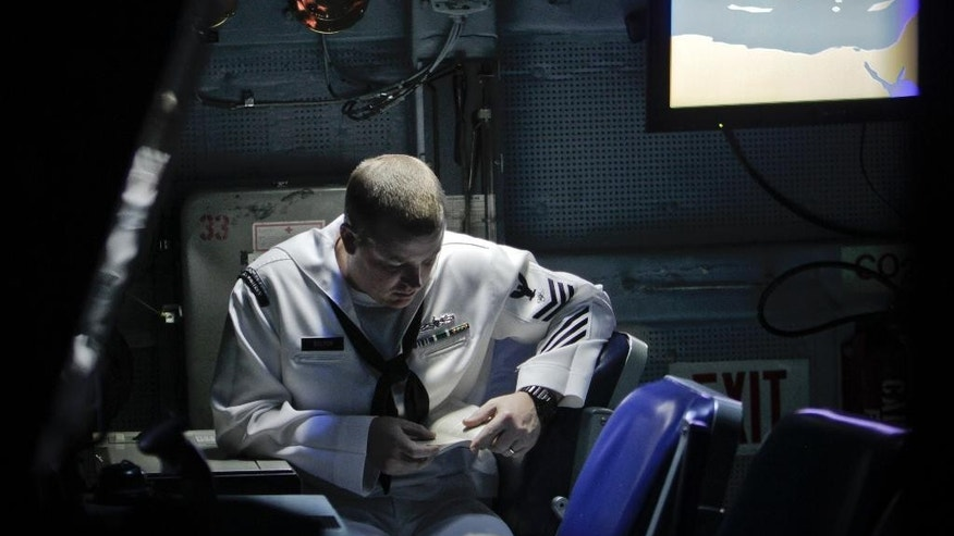 FILE- In this Tuesday, June 7, 2011 file photo, US Navy 1st Class Petty Officer Jerry Bolton, of Lesley, Michigan, reads a book on the weapons control deck of the USS Monterey, in the Black Sea port of Constanta, Romania. A U.S. missile defense system aimed at protecting Europe from ballistic missile threats is moving into higher gear this week, with a site in the village of Deveselu, Romania becoming operational on Thursday, May 12, 2016, and officials breaking ground at a separate site in Poland a day later.(AP Photo/Vadim Ghirda, File)