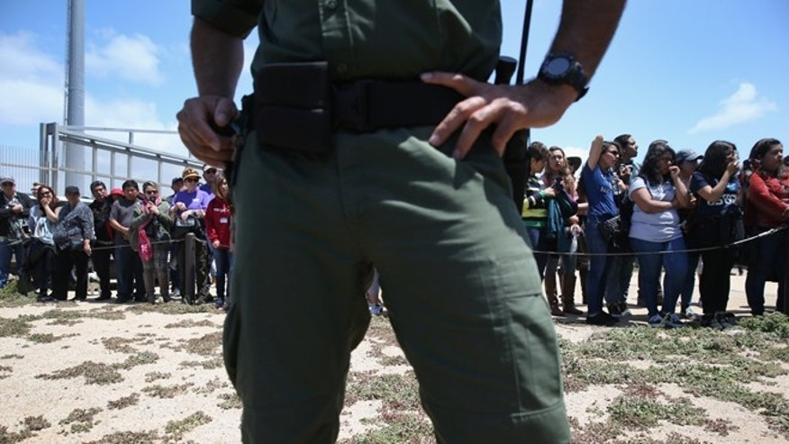 "SAN DIEGO, CA - APRIL 30:  A U.S. Border Patrol agent stands guard as families prepare to meet loved ones at the U.S.-Mexico Border fence during a ""Opening the Door of Hope"" event on April 30, 2016 in San Diego, California. Five families, with some members living in Mexico and others in the United States, were permitted to meet and embrace for three minutes each at a door in the fence, which the U.S. Border Patrol opened to celebrate Mexican Children's Day. It was only the third time the fence, which separates San Diego from Tijuana, had been opened for families to briefly reunite. The event was planned by the immigrant advocacy group Border Angels.  (Photo by John Moore/Getty Images)"