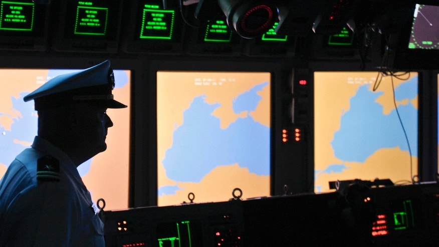 FILE- In this Tuesday, June 7, 2011 file photo, a US Navy officer, name not available, stands on the weapons control deck of the USS Monterey as screens display the Black Sea region, in the Black Sea port of Constanta, Romania.