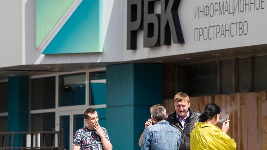 In this photo taken on Thursday, May  12, 2016, people smoke at the RBC, Media Group Russian Business Consulting firm headquarters which includes the first Russian business television company building in Moscow, Russia. Three key editors at top Russian media holding firm RBC said Friday they have resigned amid a flurry of probes and police raids around the company. (AP Photo/Alexander Zemlianichenko)